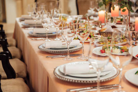 Luxurious restaurant. Luxurious interior, white tables, serving dishes and glasses for guests