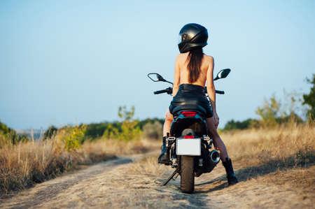 girl biker without underwear in a helmet sitting on a black motorcycle