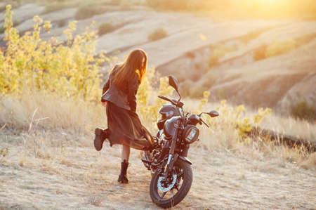 beautiful girl biker in black clothes dancing at the motorcycle Standard-Bild