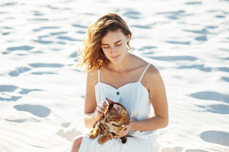 Cute girl in white dress on the beach hugs her bengal cat Standard-Bild