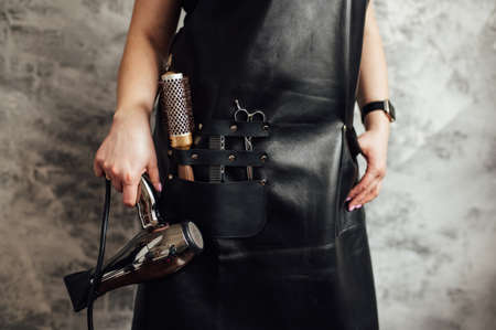 Person in black apron with professional hairdresser set on dark background, closeup
