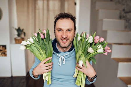 handsome man in a sweatshirt smiles and holds a bouquet of tulips in his hands