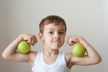 strong: boy with green apples showing biceps face Stock Photo