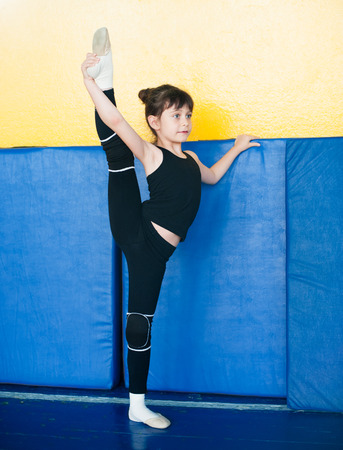 sock: girl  gymnast raised  her leg vertically up and holds it with  hand