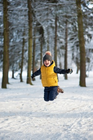 cool kids: boy jumping up in the winter forest and laughs