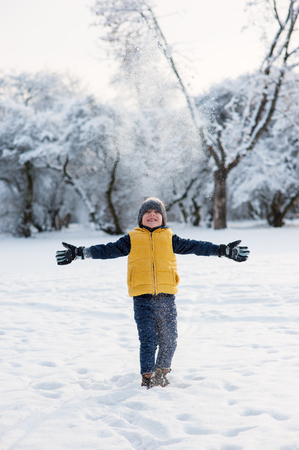 spreads: Boy throws up snow and spreads his arms to the sides in winter