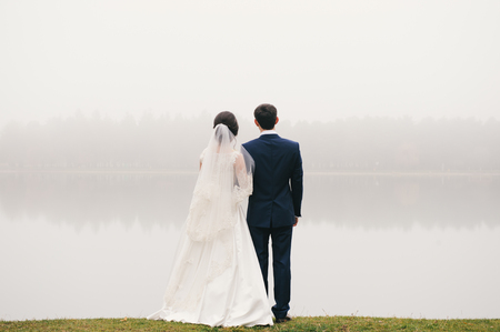 wedding celebration: bride and groom standing in front of the lake and looking into the distance in the direction of the park  Valentines Day Stock Photo