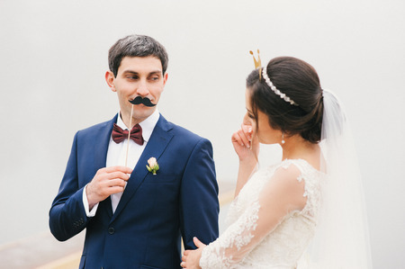 mustaches: groom attached to the face paper mustaches and bride  put her head crown and looking at each other Valentines Day
