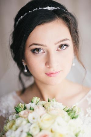 bridal salon: Portrait of  bride with a bouquet  flowers