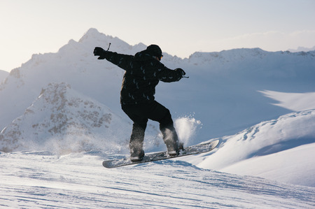 snowboarder jumping: Snowboarder jumping from a slope on a background of mountains in winter