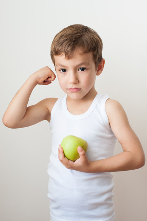 boy gymnast: kid child muscles showing strength training apple boy Stock Photo