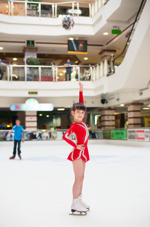 skating on thin ice: little girl skates figure skating victory sports suit smile Stock Photo