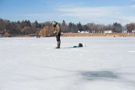 ice fishing: Fisherman on ice fishing winter