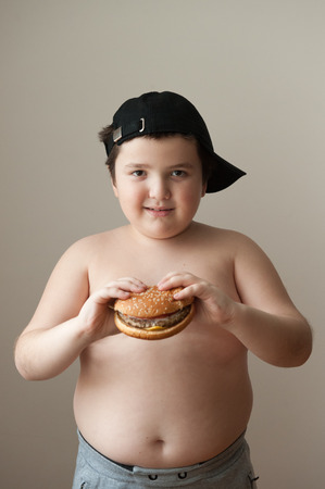 fat boy holding a hamburger and smiling Stock Photo