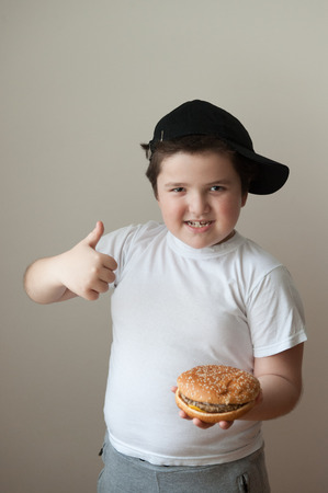 strong boy: boy holding a hamburger and raises his thumb  up