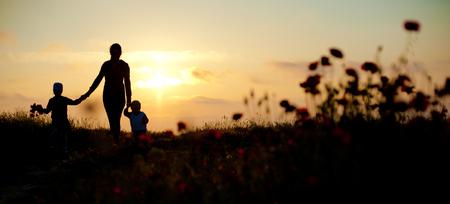mother with her children at the seaside at sunset Foto de archivo
