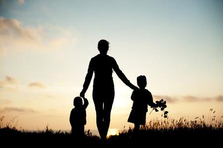 夕暮れの海辺で彼女の子供を持つ母