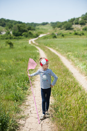 net: child with a butterfly net   is on the trail