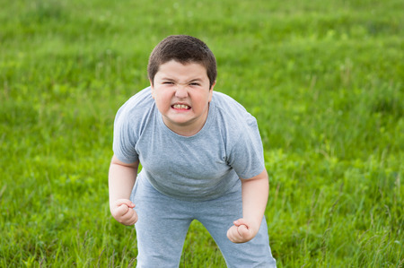 overweight kid: thick and aggressive boy looks into the frame on the background of grass Stock Photo