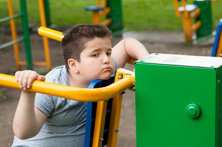 tired sad fat boy sitting on the sports simulator Foto de archivo
