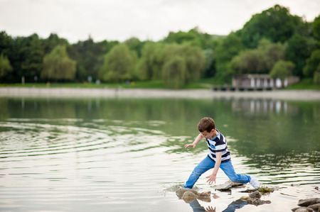 falling tide: little boy lost his balance and went into the lake Stock Photo