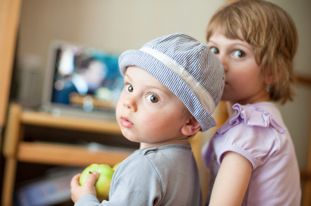 be alert: little kids turned around and looking through their shoulders Stock Photo