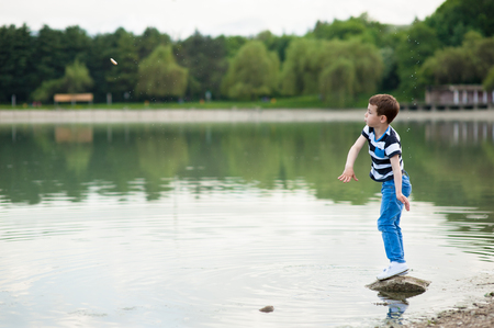active boy throws small stone into the lake Stock Photo