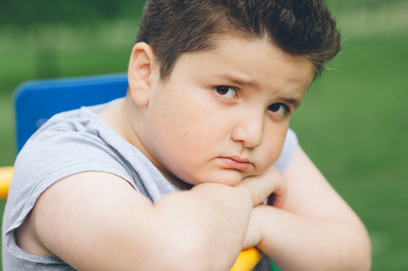 obese child: sad fat boy sitting on sports simulator