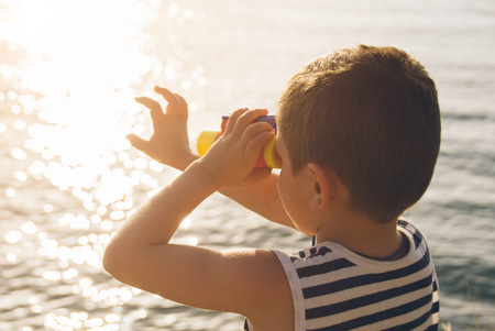 gentle dream vacation: little boy looks into the distance through binoculars and touches his hand glare on the water