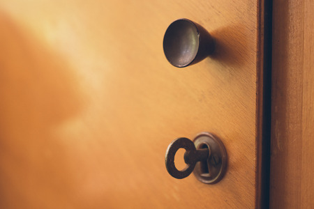 key cabinet: open door of an old wooden cabinet with lock and key Stock Photo