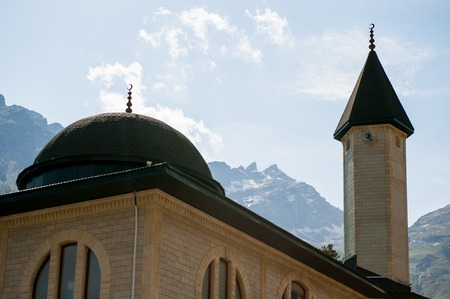 mosque on the background of snowy mountains and sky Stock Photo