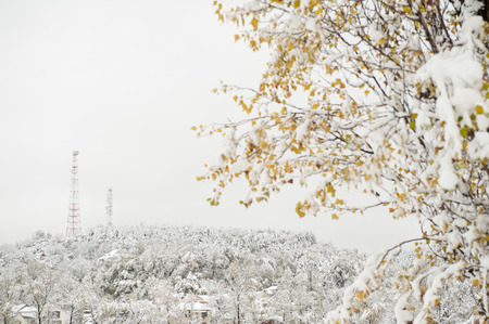 time critical: two communication antenna towers on a hill above the snow-covered village Stock Photo