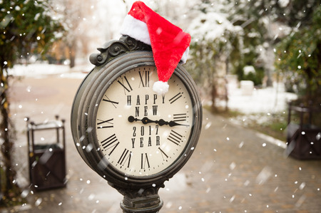 numeros romanos: vintage clock with santa hat and words Happy New Year 2017 under falling snow