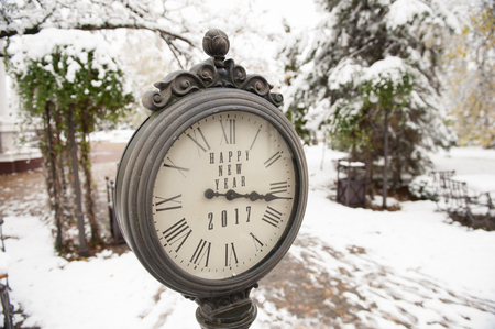 vintage clock with title Happy New Year 2017 on snowy street Stock Photo