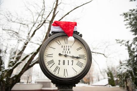 numeros romanos: reloj de la vendimia con el título de la Feliz Año Nuevo de 2017, por calle cubierta de nieve