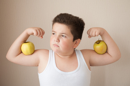 fat boy in t-shirt shows muscles with apples on his biceps