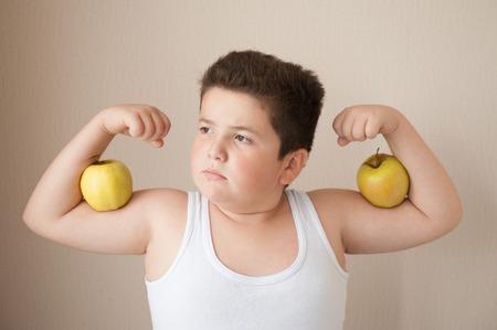 obesidad infantil: niño gordo en camiseta muestra los músculos con las manzanas en su bíceps
