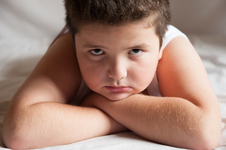 serious cute fat boy is lying and looking into camera Stock Photo