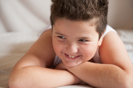 smiling beautiful fat boy lies on the bed Stock Photo