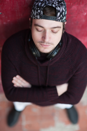 Portrait of a handsome young man in a baseball cap and in headphones on his neck on red background closing his eyes folding his arms Stock Photo