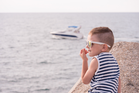 adorable little boy in a vest and sunglasses on the background of the sea and boat