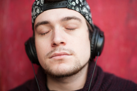 Portrait of a handsome relaxing young man in a baseball cap and wearing headphones on a red background