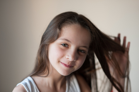 smiling little girl straightens her hair with one hand