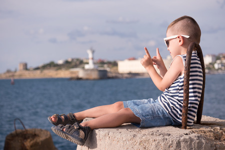 small boy in a vest and shorts sitting on a breakwater on the background of the sea and the shore with a beacon lifting two fingers up
