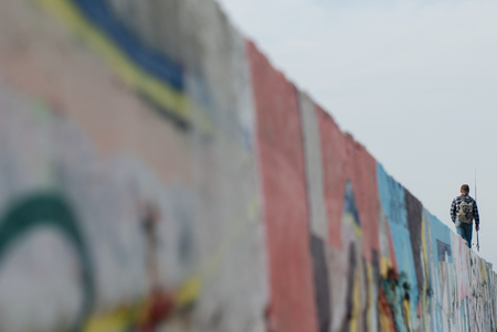 one man with fishing rod and backpack goes fishing walking on wall with graffiti Stock Photo