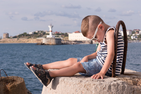 cute little boy in sunglasses and a vest sitting on concrete breakwater with sea and shore with lighthouse background Stock Photo