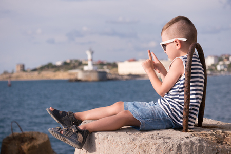 little boy in a vest and shorts sitting on a breakwater on the background of the sea and the shore with a beacon lifting two fingers up Stock Photo