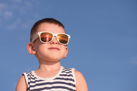 smiling little boy wearing white sunglasses with sea sunset reflection and sailor stripes shirt on blue sky background with copyspace