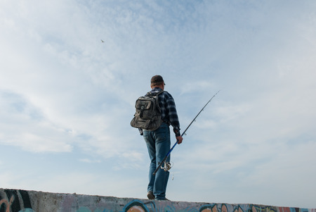 adult male with a fishing rod and a backpack goes fishing Stock Photo