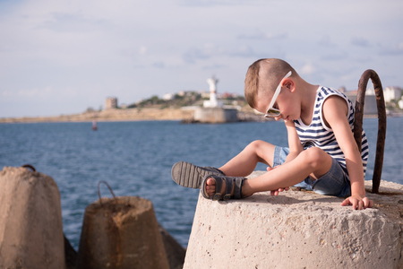beautiful little boy in sunglasses sits on a concrete breakwater against the background of the sea and the shore with lighthouse